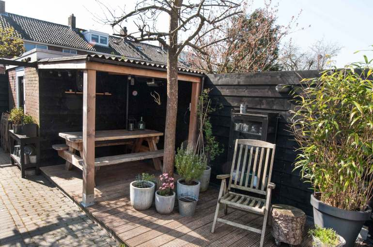 My garden with a n indoor picknick table, plants in pots and a big bamboe plant