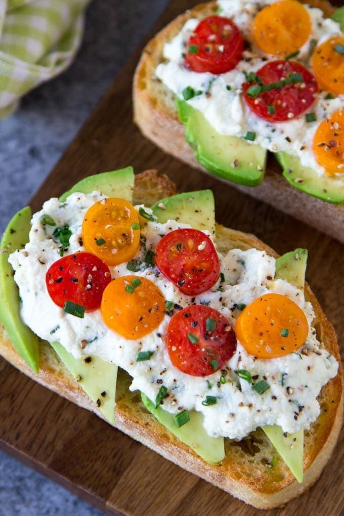 Avocado Toast + Herbed Ricotta & Fresh Tomatoes- Crusty Artisan bread toasted and topped with creamy avocado, herbed ricotta (ricotta with spinach, basil, red pepper flakes and chives) and Fresh Tomatoes. A crowd pleaser and it only takes 5 min. to make.