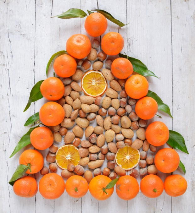 christmas tree of mandarins and nuts on old grunge wooden board