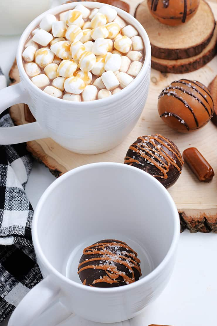 SIMPLE Caramel Flavored Hot Cocoa Bombs - a beautiful way to serve hot cocoa with a chocolate sphere filled with cocoa powder and mini marshmallows #hotococoabomb