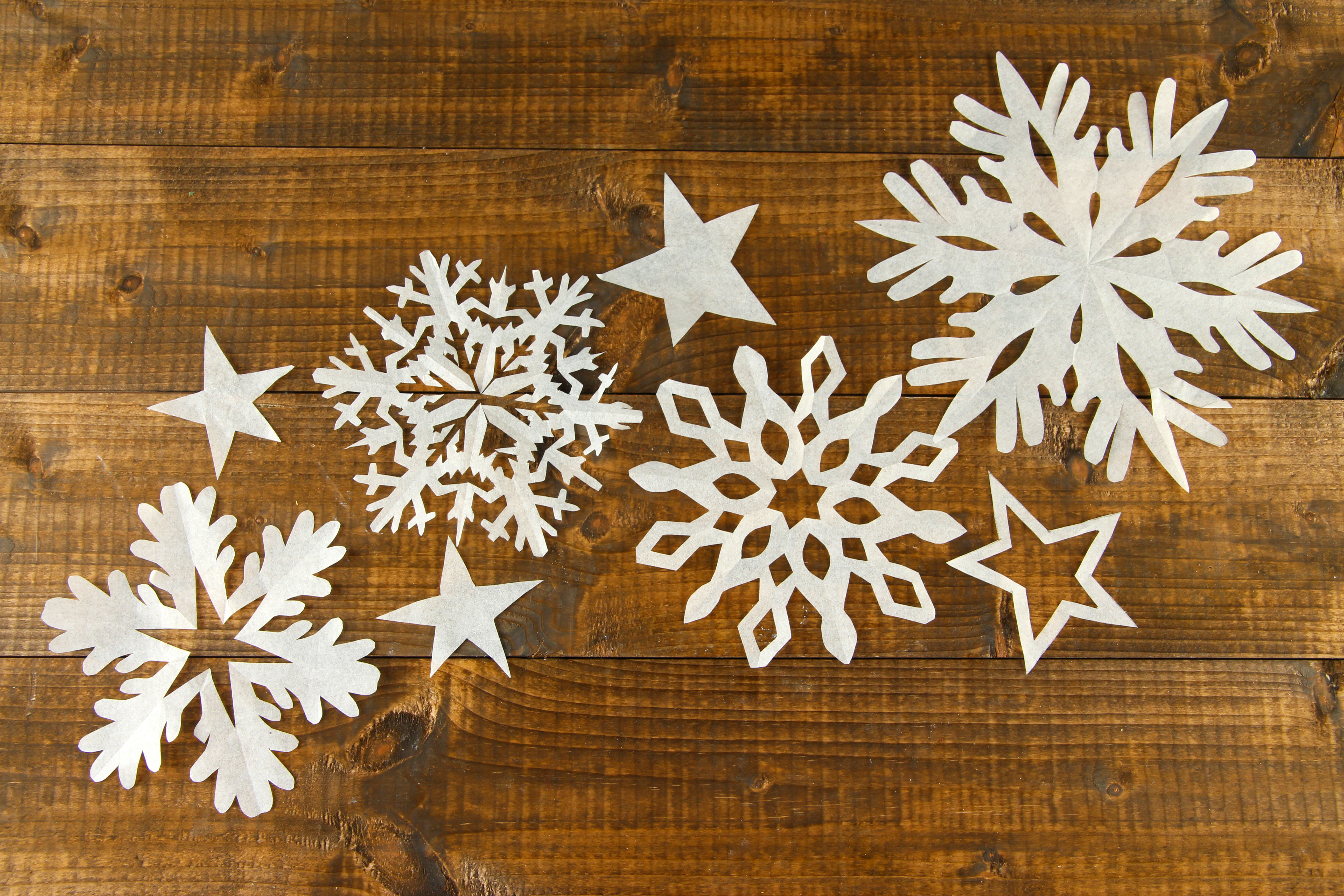 Beautiful paper snowflakes on wooden background