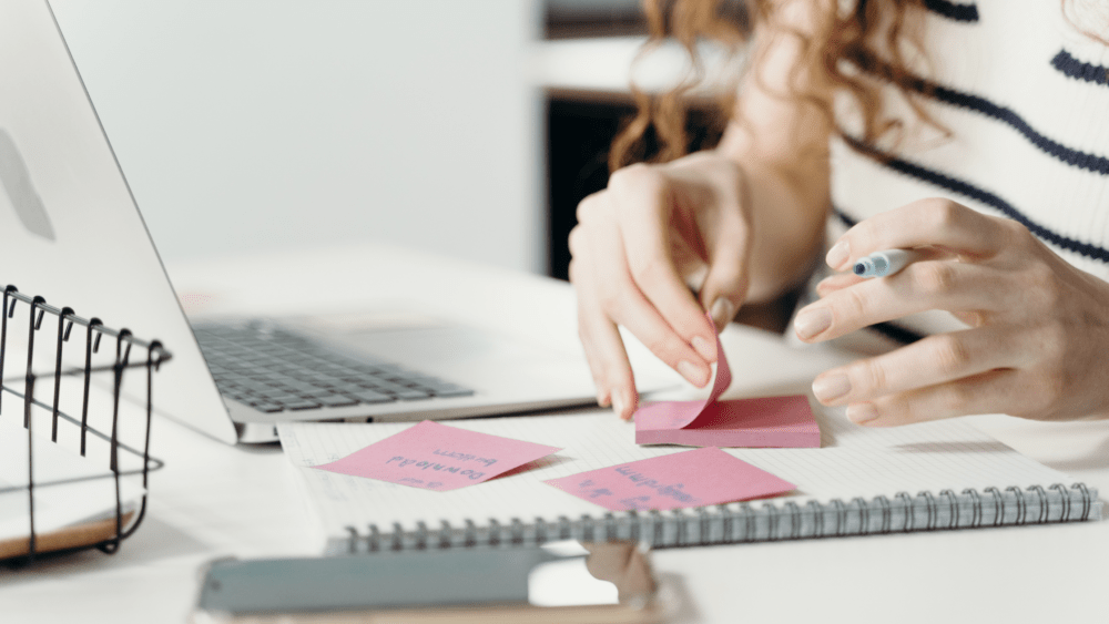 woman organising sticky notes in front of her laptop