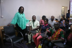 Mrs Fayo Williams taking photograph with people living disability in class