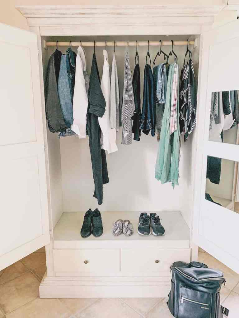 A winter capsule wardrobe hanging in a white closet.