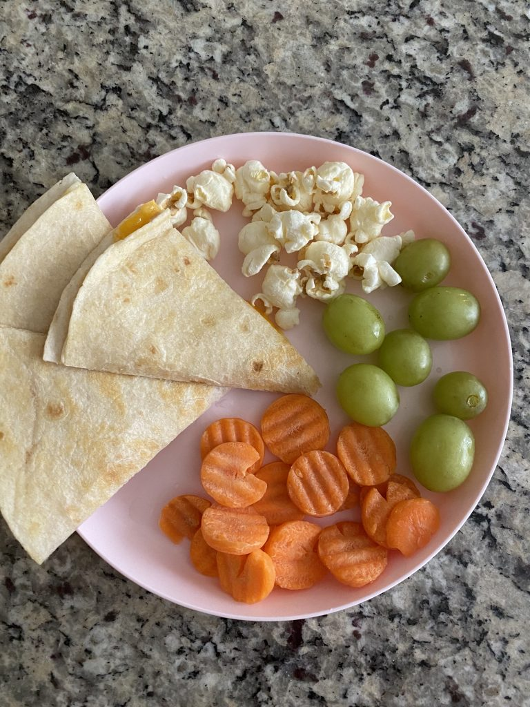 lunch in 1/4s popcorn, cheese quesadilla,grapes, carrots on a plate