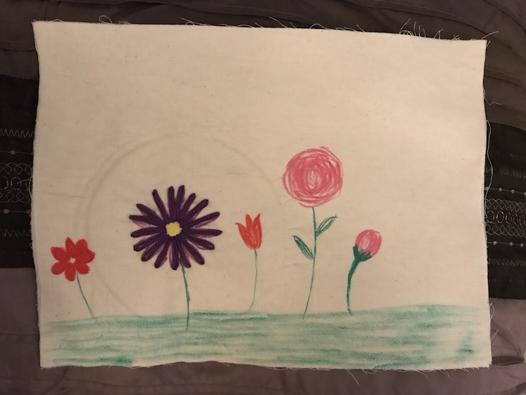 I colored in the grassy ground and a couple flowers on my quiet book page. I then used an embroidery hoop to keep the page taunt but with the interfacing it ended up leaving a mark for a couple days before it disappeared.