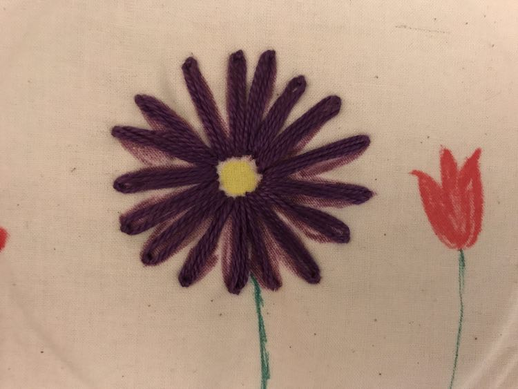 I kept this flower simple so you could see the background fabric marker colors. I kept the center of the flower empty to let the yellow shine through. I then matched the purple and used a detached chain stitch for elongated petals overtop of the purple fabric marker petals.