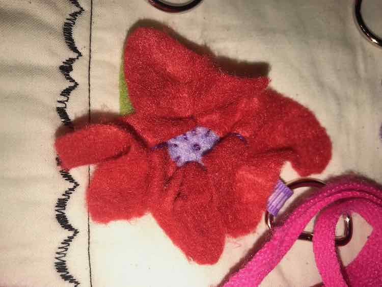Sewed down the flower by going around the outside of the center and then added a french knot to the beginning. The petals are shaped by adding some stitches to the center of them and pulling it a bit tight.