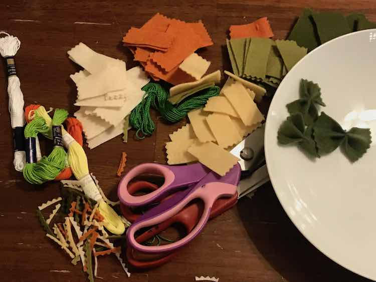 All the steps in making the pasta is shown. To the left is the embroidery floss and cut off crinkles. The center shows the rectangular felt pieces with the crinkled ends along with my pinking shears and fabric scissors. To the right is a bowl with three perfectly green bow-tie pasta.