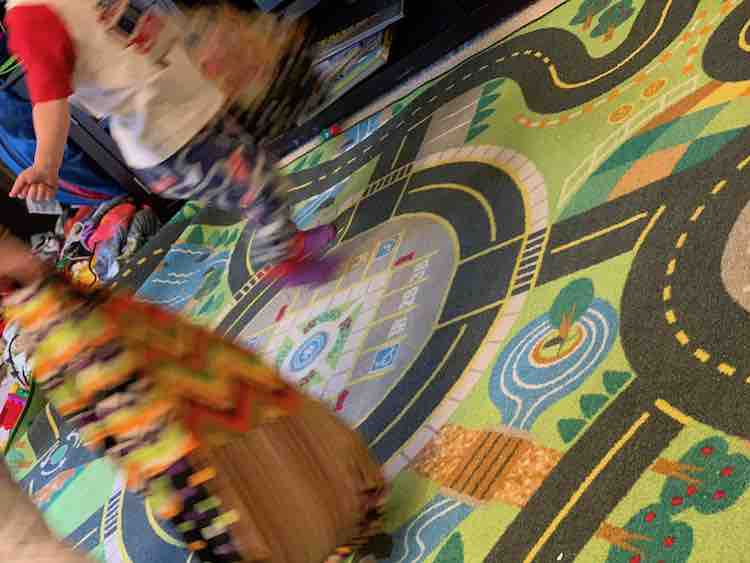Kids running around the road track floor mat while carrying the market bags.