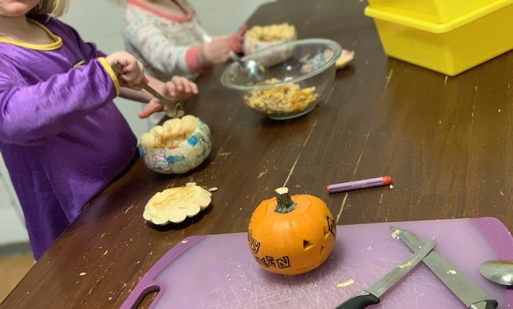 We started by cutting the tops off of the pumpkins (me), and then using grapefruit spoons and our fingers to pull out the guts. I carved a small and simple face on my pumpkin and gave Ada a crayon to mark hers. I ended up cutting a simple heart on Ada's and left Zoey's plain as I realized the solution might spill out from the cut holes before it could be mixed.