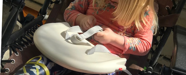 Ada sits in the chair focused on the three point buckle system on the highchair's back rest.