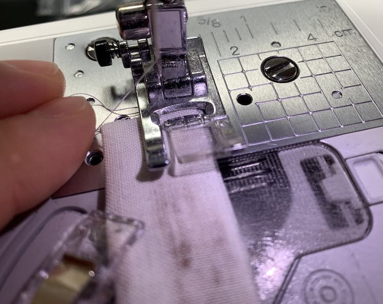 Sew your strap closed while keeping the thread out of the way.