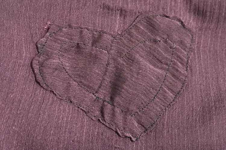 Closeup of the heart shows the lines going angled across rather than down like the base camisole. No tape is showing through the heart and the stitches are keeping the heart in place.