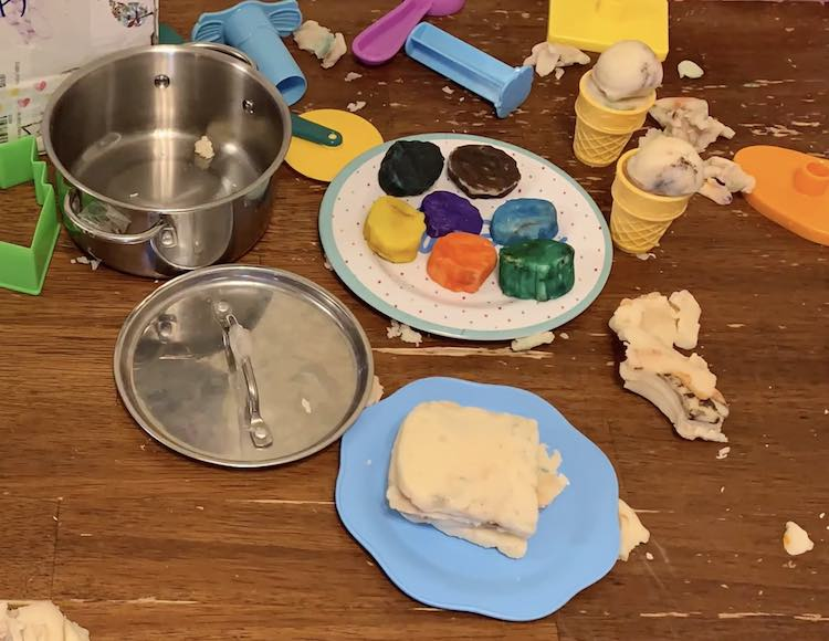 Empty pot, playdough sandwich on a blue plate, plate of several different hued solid colored cookies, and two ice cream cones.