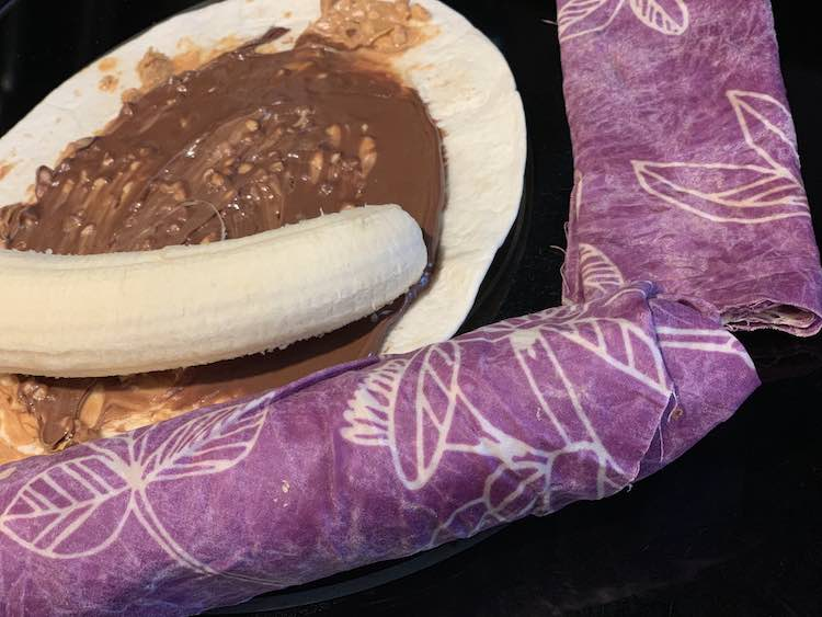 Banana about to be wrapped in chunky peanut butter, Nutella, and the tortilla wrap. Finished and fully wrapped wrap beside the half finished one.