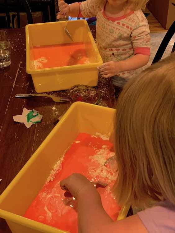 Ada and Zoey playing with red and orange oobleck.