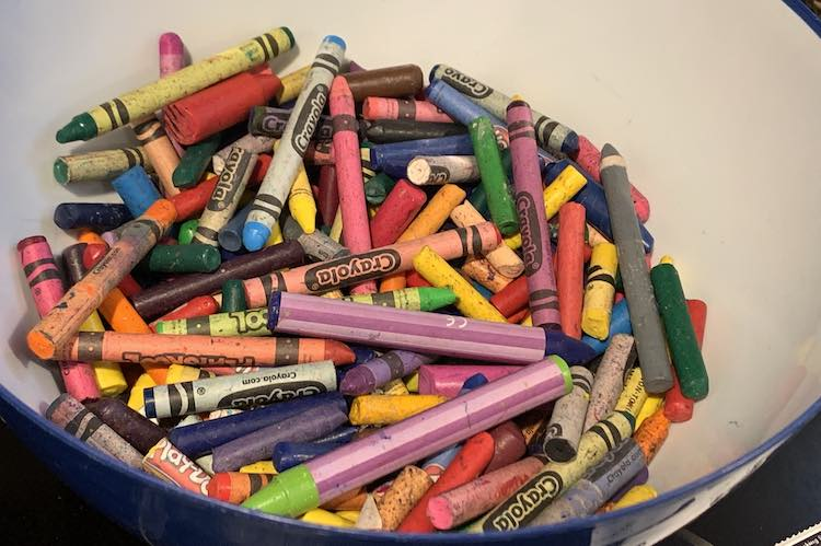 Plastic bowl half fulled all our excess crayons.