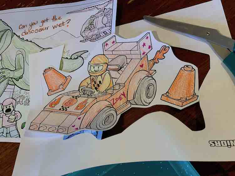 Cut out and colored race car in the foreground with the outer paper, scissors, and a whole dinosaur coloring page in the background.
