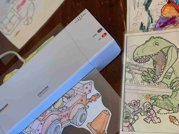 Laminating in progress with some finished and waiting coloring pages sprinkled around it.