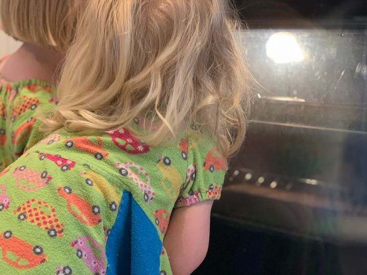 Ada and Zoey staring into the lit up oven watching the crayons slowly melt.