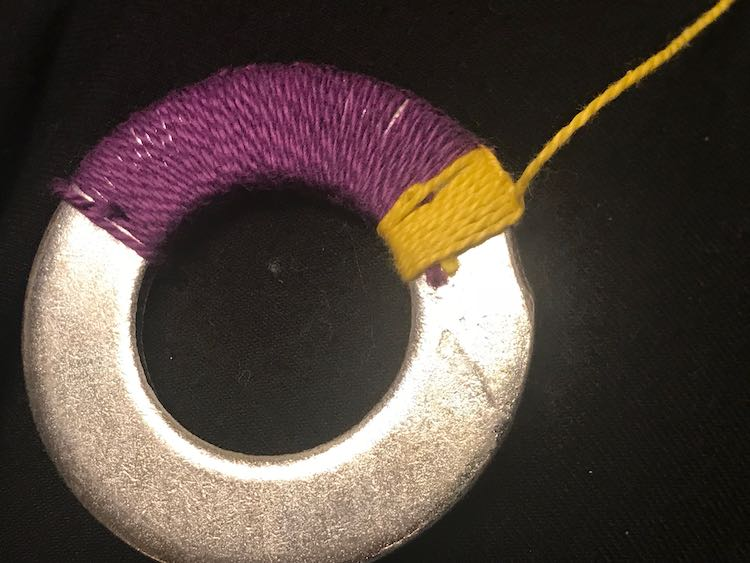 Large swash of purple embroidery floss looped around the washer next to a small section of yellow. At the edge of the yellow section you can see the purple and yellow tips of the loose ends sticking out. The next loop/knot around the washer will hide them.