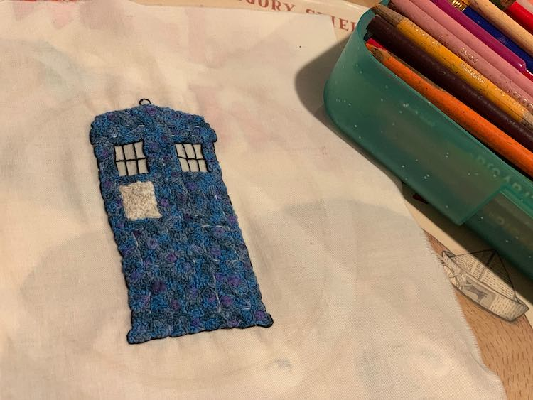 Finished TARDIS laid out with an open container of pencil crayons beside it.