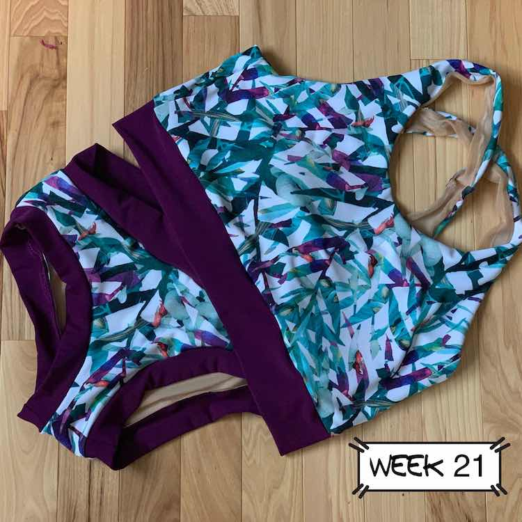 Front of the swimming suit with the top slightly overlapping the top corner of the swim bottoms. Main fabric is white with teal and purple leaves. The bands are all eggplant to match the purple in the main fabric.