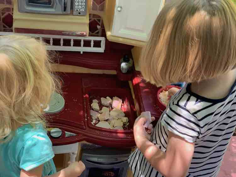 Kids in front of a kitchen set. Sink has flat chunks of dried up oobleck while Ada stands in front of a frying pan of 'sand' holding an unbroken piece in her left hand.