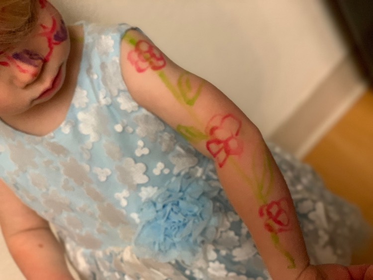 Zoey wearing a blue dress with white flowers. There's a green stem with pink flowers going up her arm and surrounding her eye.