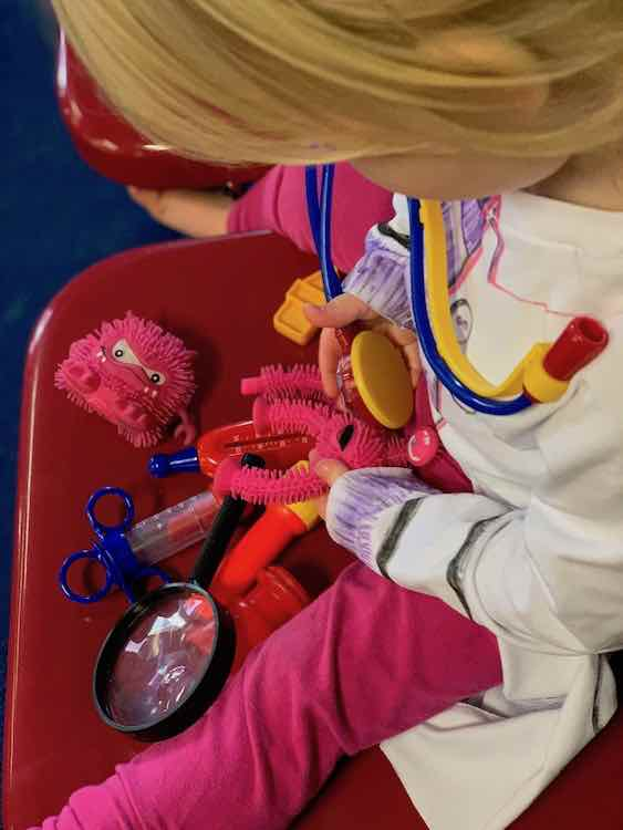 Zoey sitting on a red chair with two squeeze toys (one missing a leg) and her doctor tools. She's giving a checkup to the monster missing a leg.
