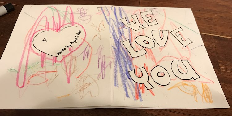 """View of both the front and back of the card. The heart has a triangle drawn on the left (for a light spot) and a label """"Kards by Kyra & Ada""""."""