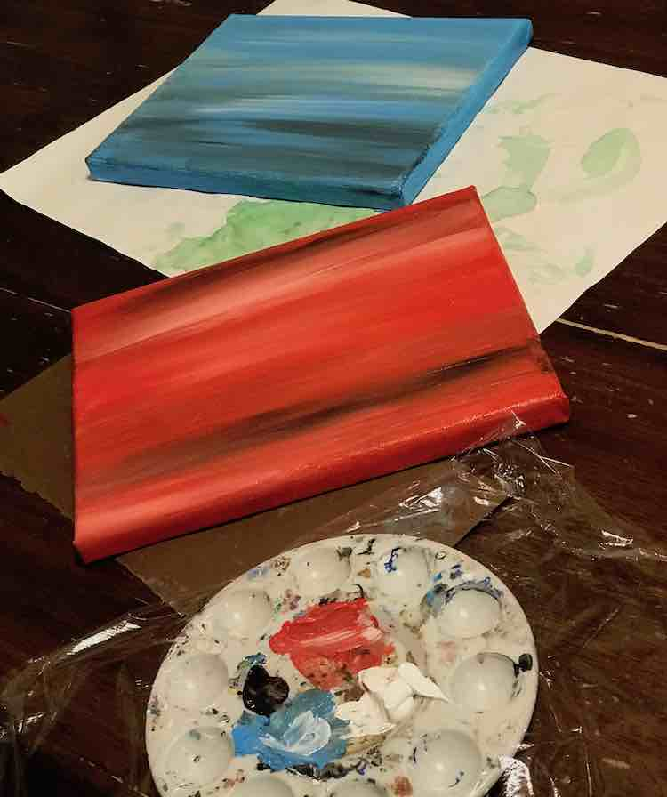 Vertical image with the blue canvas at the top, the red in the middle, and the used paint palette with plastic wrap laid overtop.