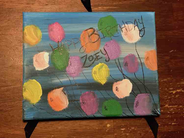 """Blue sign showing """"Happy Birthday Zoey"""", a group of balloons, and a blue streaked background."""
