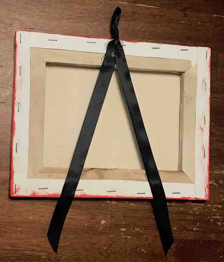 Back view of the canvas shows all three points the ribbon is glued to the canvas.