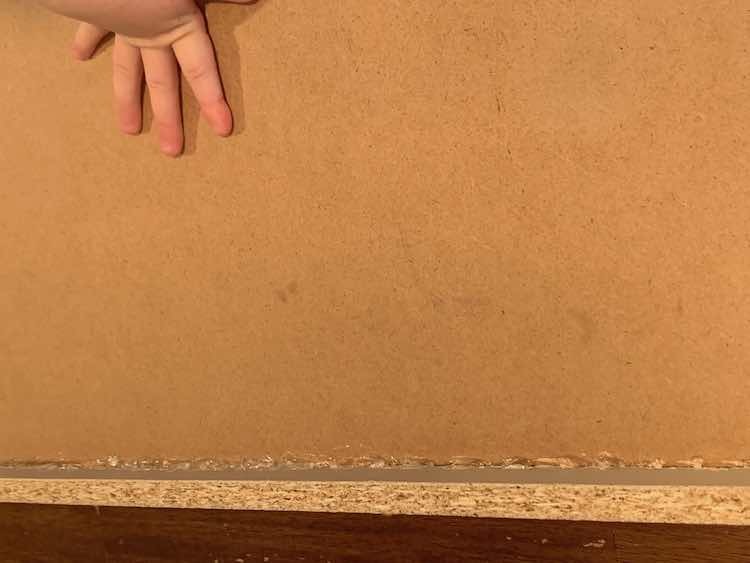 Closeup of the bottom of the dresser drawer. The bottom of the picture shows the glue holding the drawer base in the frame. The top of the picture shows Zoey's hand holding the drawer base in place.