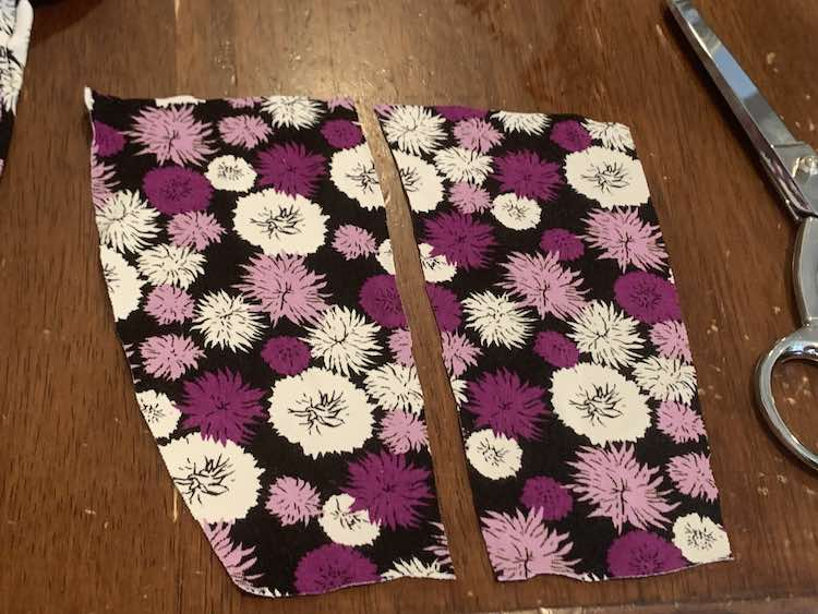 Scrap of fabric sitting on the table. It'd cut in half and slightly pulled apart. The right piece is a smooth rectangle while the leftmost one has a curved left side making the top larger than the bottom. My scissors rest beside the fabric.