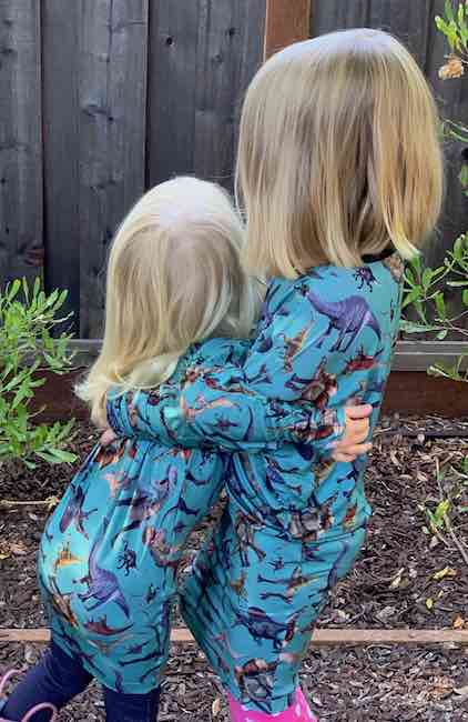 Hugging while wearing the dinosaur dresses.