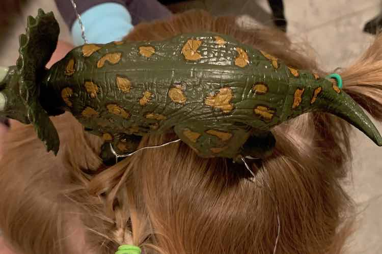Side view of the triceratops on Ada's head. The front (bottom left in the image) leg is secured by French braiding the wire into place. The bottom of the image shows the lime green hair tie used to keep the braid secure. The second braid is hidden behind the dinosaurs tail but you can see it's hair tie right above the tail.