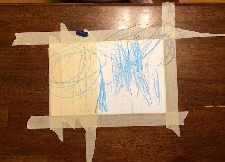Taped down card on a table showing a square of white. There's a blue crayon laying on the card and blue scribbles over the entire thing.