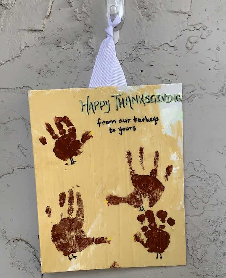 "The ""Happy Thanksgiving from our turkeys to yours"" sign is hung up and showing off the girls little hand prints."