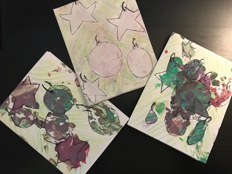 Three cards are in the image. The middle one has very faint, almost white, ornaments while the other two are more bold in green and burgundy.