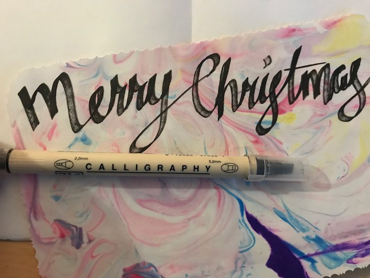"""Merry Christmas"" written across the top of the marbled paper with an opened blank card behind it."