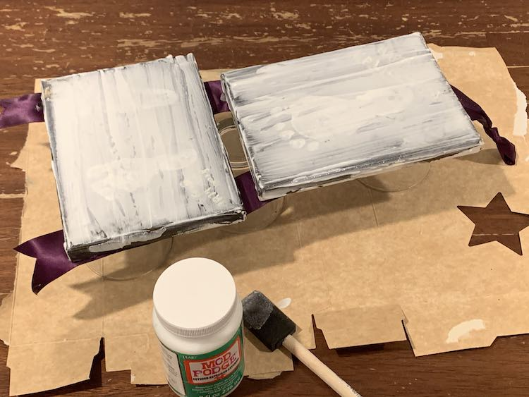 The bottom of the glasses are just peeking out from under the balanced canvases. You can hardly see the image on the canvas as the mod podge is spread on and white right now. Used foam brush and bottle of mod podge are at the bottom of the photo.