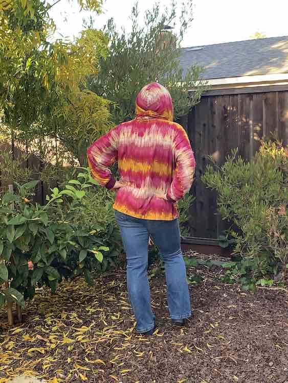 This image is a bit further away showing the back of the hoodie with the hood on.