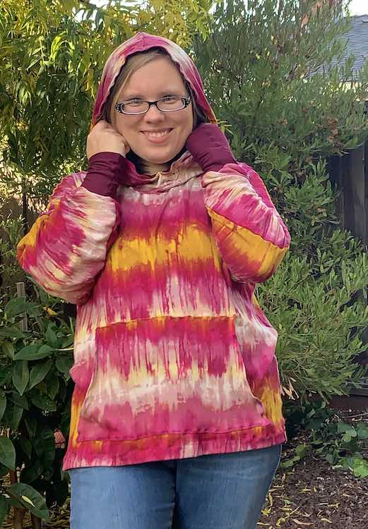 Front view of the hoodie with the hood on over my head. My arms are upright holding onto the hood which better shows off the cuff at the end of the sleeves.