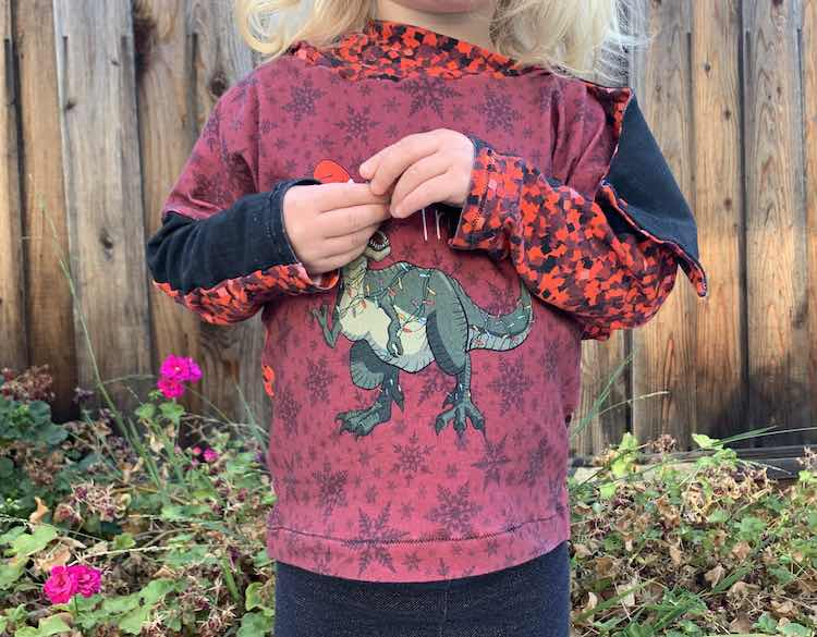 "Closeup of the front of Zoey's hoodie with her arms up in front of the ""Tree Rex"" showing her sleeves and with the flap showing over her arm from the lowered hood hanging behind her."