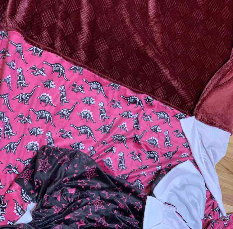 Flat lay showing the dinosaur fabric sewn to the bottom of the Costco throw. The original hemline adds the appearance of topstitching near the seam.