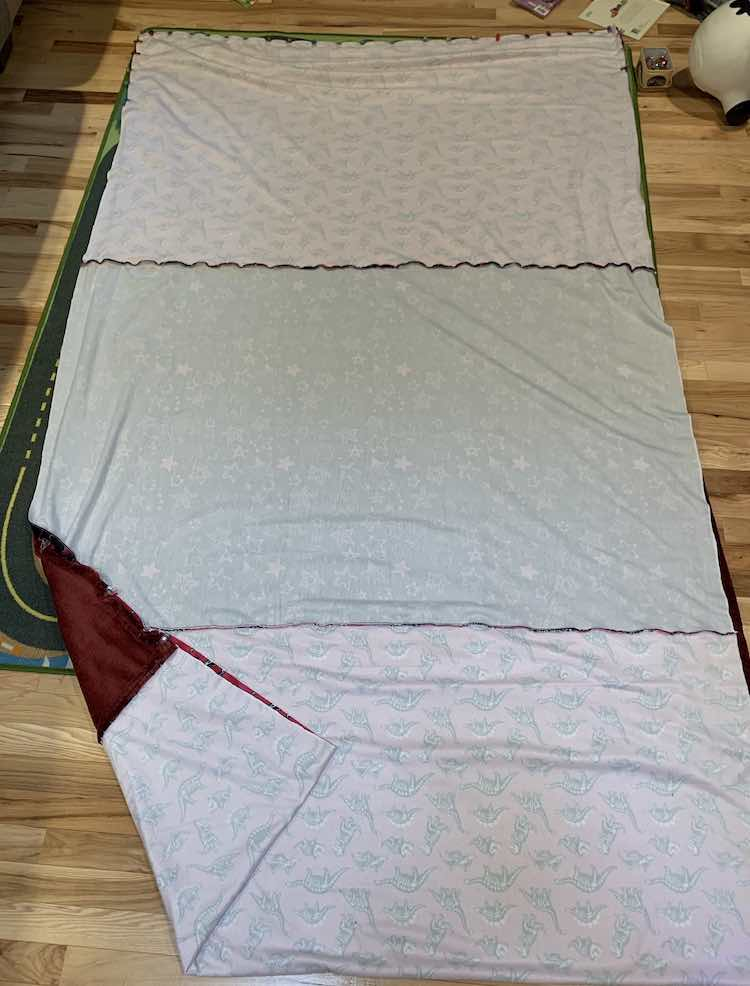 Photo looks down at the wrong side of the sewn together dinosaur and star fabric. The bottom of either fabric (show at the top) is clipped together while the sides are not yet.