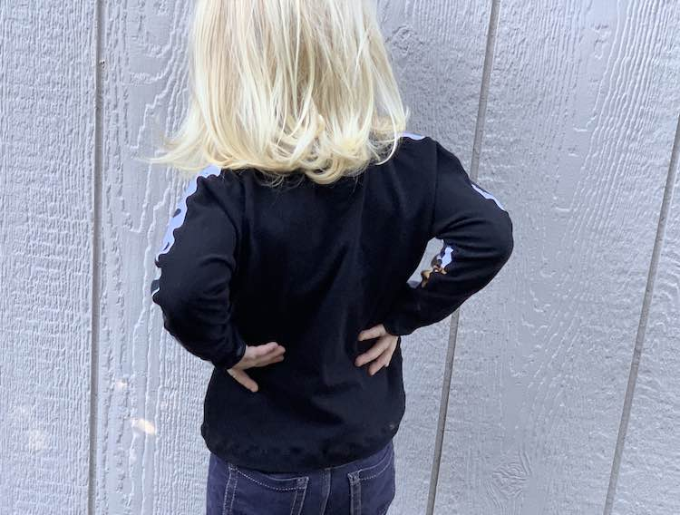 Back view of the pumpkin shirt. Zoey's hands are on her hip and you mostly see the black fabric.